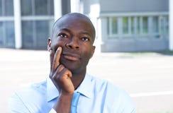 Homme d'affaires africain de pensée devant son bureau Image libre de droits