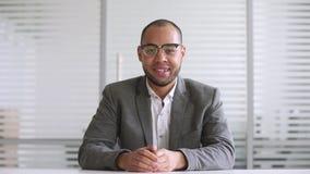Homme d'affaires africain de sourire regardant le webcam pour faire la conférence téléphonique en ligne clips vidéos