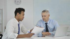 Homme d'affaires africain Discussing Project Documents avec Grey Hair Businessman supérieur banque de vidéos