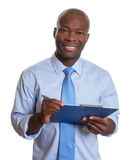 Homme d'affaires africain faisant des notes Images stock