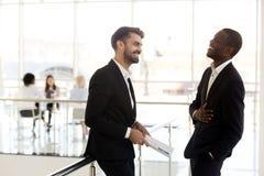 Homme d'affaires africain gai riant de la plaisanterie drôle du Caucasien photos libres de droits