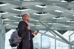 Homme d'affaires africain heureux avec le téléphone portable et le sac Photographie stock