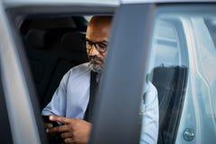 Homme d'affaires africain mûr à l'aide du smartphone dans la voiture photo libre de droits