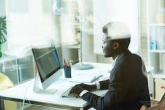 Homme d'affaires africain réussi utilisant le PC photo libre de droits