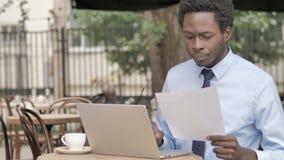 Homme d'affaires africain Reading Contract et ordinateur portable d'utilisation en café extérieur clips vidéos