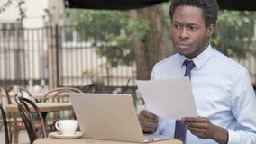 Homme d'affaires africain Reading Documents tout en se reposant en café extérieur banque de vidéos