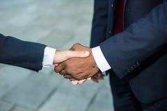 Homme d'affaires africain serrant la main à caucasiens Images libres de droits