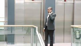 Homme d'affaires afro-américain au téléphone dans un bâtiment banque de vidéos