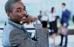 Homme d'affaires d'afro-américain avec des cadres fonctionnant à l'arrière-plan Photographie stock libre de droits