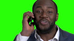 Homme d'affaires afro-américain enthousiaste parlant au téléphone clips vidéos