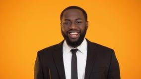 Homme d'affaires afro-américain faisant le faux sourire, émotions pas sincères, compagnon ennuyé banque de vidéos