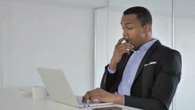 Homme d'affaires afro-américain occasionnel choqué Working sur l'ordinateur portable, étonné clips vidéos
