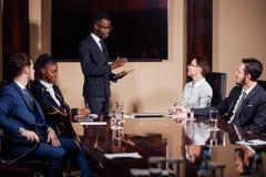 Homme d'affaires d'afro-américain présentant l'exposé aux associés photos libres de droits