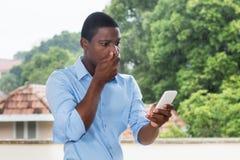 Homme d'affaires d'afro-américain recevant le message textuel avec mauvais nouveau photographie stock libre de droits