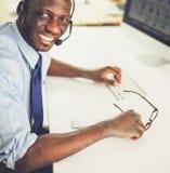 Homme d'affaires d'afro-américain sur le casque travaillant sur son ordinateur portable image stock