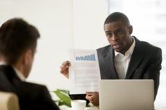 Homme d'affaires afro-américain tenant les graphiques en hausse, présentant le repo Photos stock