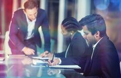 Homme d'affaires agissant l'un sur l'autre avec des collègues lors de la réunion Photographie stock libre de droits