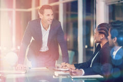 Homme d'affaires agissant l'un sur l'autre avec des collègues lors de la réunion Photos stock