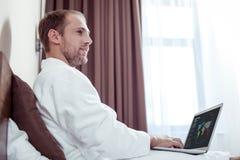 Homme d'affaires agréable bel travaillant dans le lit pendant le matin images libres de droits