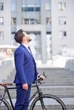 Homme d'affaires agréable se tenant avec la bicyclette images stock