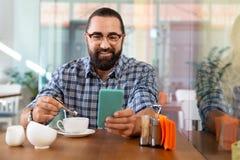 Homme d'affaires agréable vérifiant l'email au téléphone ayant la pause-café photographie stock