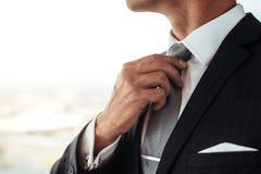 Homme d'affaires ajustant le sien regard photographie stock libre de droits