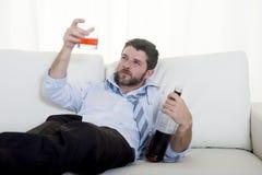 Homme d'affaires alcoolique dans le lien lâche bu gaspillé sur le divan à la maison Photos libres de droits
