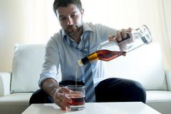 Homme d'affaires alcoolique portant le remplissage bu par chemise bleue vers le haut du verre de whiskey Photos stock