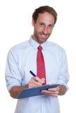 Homme d'affaires allemand riant avec le presse-papiers Image libre de droits