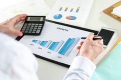 Homme d'affaires analysant des bilans financiers Image stock