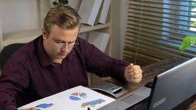 Homme d'affaires analysant des graphiques et des diagrammes et comptant la calculatrice, sur une table en bois banque de vidéos
