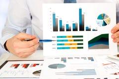 Homme d'affaires analysant des graphiques et montrant des graphiques par le stylo Image stock