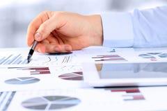 Homme d'affaires analysant des graphiques et montrant des graphiques par le stylo Images stock