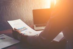 Homme d'affaires analysant le graphique financier de statistiques au bureau photo stock