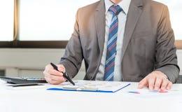 Homme d'affaires analysant le rapport, concept de rendement de l'entreprise Images stock