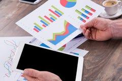 Homme d'affaires analysant les diagrammes financiers photographie stock