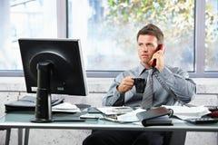Homme d'affaires appelant au bureau avec la tasse Images libres de droits