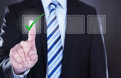 Homme d'affaires appuyant sur le bouton de coche Photographie stock libre de droits