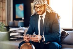Homme d'affaires arabe comptant l'argent sur le divan à la chambre d'hôtel photos libres de droits