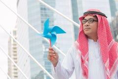 Homme d'affaires arabe jouant avec les moulins à vent de papier Photos stock