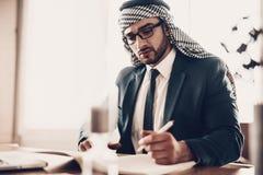 Homme d'affaires arabe prenant le carnet des notes n à la table images libres de droits