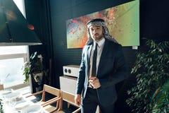 Homme d'affaires arabe tenant la table de dîner proche à la chambre d'hôtel photographie stock