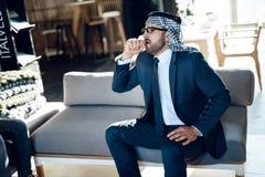 Homme d'affaires arabe toussant se reposer sur le divan à la chambre d'hôtel photos libres de droits
