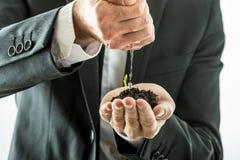 Homme d'affaires arrosant et consolidant une pousse verte s'élevant d'a images stock