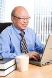 Homme d'affaires asiatique aîné travaillant Images stock