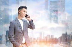 Homme d'affaires asiatique au téléphone dans une ville Image stock