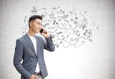 Homme d'affaires asiatique au téléphone, flèches Photos stock