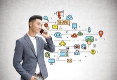 Homme d'affaires asiatique au téléphone, media social Image stock
