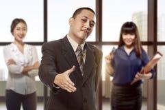 Homme d'affaires asiatique bel avec la main ouverte prête pour la secousse de main Photos libres de droits