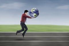 Homme d'affaires asiatique dans la course avec la terre images stock